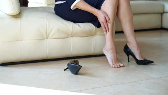 Cropped image of woman in black high heels massaging her tired legs, suffering from varicose vein pain